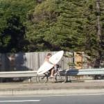 Серфер- на велосипеде на пляж с доской
